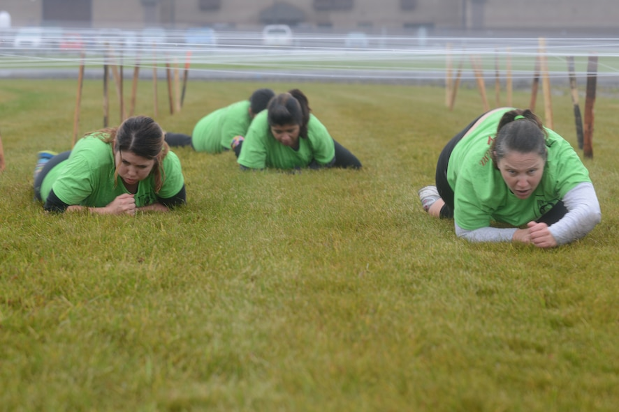 """Members from """"Team Awesome Salsa"""" low crawl through an obstacle during the POW/MIA Combat Challenge Sept. 16, 2015, at Eielson Air Force Base, Alaska. The challenge gave participants a sense of camaraderie and teamwork while overcoming the stress of each obstacle. (U.S. Air Force photo by Senior Airman Ashley Nicole Taylor/Released)"""