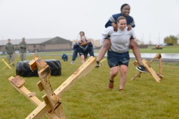 """Members with the """"AMMO's All-female Power Team"""" carry teammates through an obstacle during the POW/MIA Combat Challenge Sept. 16, 2015, at Eielson Air Force Base, Alaska. The challenge required every member to complete each obstacle before moving onto the next one. (U.S. Air Force photo by Senior Airman Ashley Nicole Taylor/Released)"""