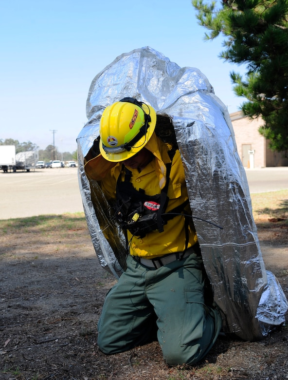 Senior Airman Ronald Skala, 30th Civil Engineer Squadron heavy equipment operator, demonstrates the use of a Fire Shelter, Sept. 21, 2015, Vandenberg Air Force Base, Calif. Constructed of aluminum foil, silica and fiberglass, a fire shelter is designed to protect the individual from smoke, heat and flames. (U.S. Air Force photo by Senior Airman Kyla Gifford/Released)