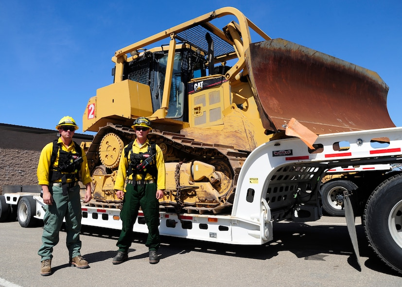 Senior Airmen Ronald Skala and Thomas Williams, 30th Civil Engineer Squadron heavy equipment operators, stand in front of a fire dozer, Sept. 21, 2015, Vandenberg Air Force Base, Calif. The fire dozer team is on stand-by during every launch, prepared to contain fires that start and prevent damage to base assets. (U.S. Air Force photo by Senior Airman Kyla Gifford/Released)