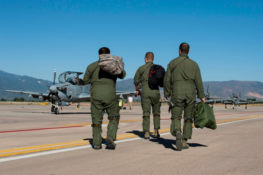 Two pilots from the 81st Fighter Squadron out of Moody Air Force Base, Ga., and an Afghan pilot walk to several A-29B Super Tucanos to prepare for high-altitude training Sept. 16, 2015, at Peterson Air Force Base, Colo. Four Afghan pilots have been training with the 81st FS on the aircraft since January in Georgia and came to Peterson to experience high-altitude and mountainous terrain. After completing their training in the U.S., both the American and Afghan pilots will go to Afghanistan to help establish fighter squadrons. (U.S Air Force photo/Airman 1st Class Rose Gudex)