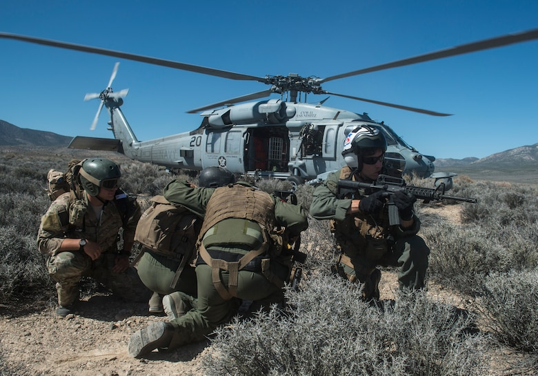U.S. Air Force Senior Airman Dane Dougherty, 335 Training Group Survival, Evasion, Resistance and Escape specialist and Capt. Jack Green, 480 Fighter Squadron F-16 pilot run to a Sikorsky HH-60 Pave Hawk at the Nevada Test and Training Range, Nevada July 30, 2015. During Red Flag 15-3 the Pave Hawk was used to rescue a simulated downed pilot. (U.S. Air Force photo by Brittany A. Chase)