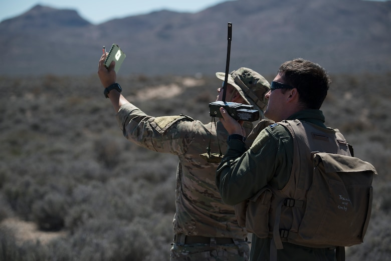U.S. Air Force Senior Airman Dane Dougherty, 336 Training Group Survival, Evasion, Resistance and Escape specialist, demonstrates how to use a mirror flash while Capt. Jack Green, 480 Fighter Squadron F-16 pilot, uses a radio Jul 30, 2015 at the Nevada Test and Training Range, Nevada. Doughetry assisted and evaluated Green, who was simulating a downed pilot, during Red Flag 15-3. (U.S. Air Force photo by Senior Airman Brittany A. Chase)
