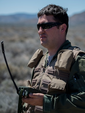 U.S. Air Force Capt. Jack Green, 480 Fighter Squadron F-16 pilot, holds a radio/signal transmitter July 30, 2015 at the Nevada Test and Training Range, Nevada. Green, who was simulating a downed pilot during Red Flag 15-3, used various methods to help pilots overhead pin-point his location in order to be saved. (U.S. Air Force photo by Senior Airman Brittany A. Chase)