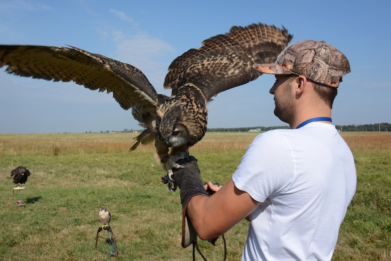 Kamil Domanski, a falconer, holds up an owl as part of the Bird/Wildlife Aircraft Strike Hazard prevention program at Lask Air Base, Poland, Sept. 14, 2015. Domanski assists the base's BASH program to reduce any collision between wild birds and aircraft, which can result in millions of dollars in damage each year. (U.S. Air Force photo by Master Sgt. Paul Gorman/Released)