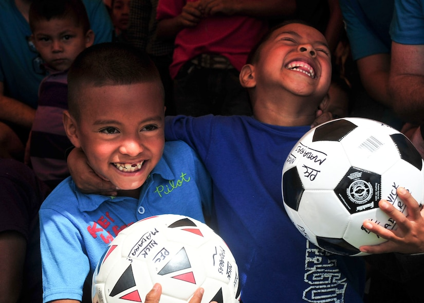 SOTO CANO AIR BASE, Honduras – Two school-age boys laugh as they hold new soccer balls during the 63rd Joint Task Force-Bravo Chapel Hike in Calavera Centro, Honduras, Sept. 19, 2015. Volunteers from JTF-Bravo distributed these soccer balls, and a number of others, to schools in this remote, mountain village as part of a larger humanitarian assistance and partnership-building event. (U.S. Air Force photo by Capt. Christopher Love)