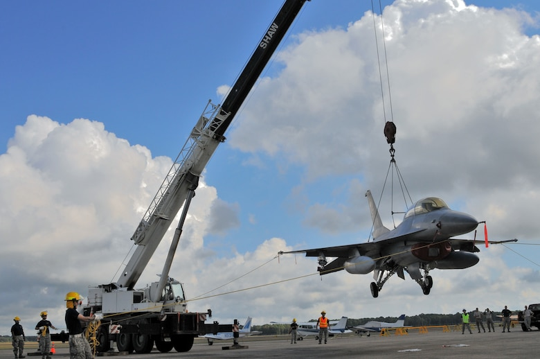 U.S. Air Force airmen from the New Jersey Air National Guard 177th Fighter Wing Crash Disabled Damaged Aircraft Recovery team maneuver an F-16 Fighting Falcon hooked up to a crane, Sept. 19, 2015 at Naval Air Station Wildwood Aviation Museum, N.J. The CDDAR team completed crane lift training, a tri-annual certification used in the event an immobile aircraft needs to be removed from a runway quickly and safely. (U.S. Air National Guard photo by Senior Airman Shane S. Karp / released)