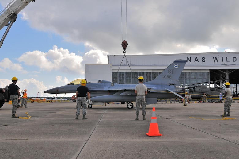 U.S. Air Force airmen from the New Jersey Air National Guard 177th Fighter Wing Crash Disabled Damaged Aircraft Recovery team maneuver an F-16 Fighting Falcon hooked up to a crane lift, Sept. 19, 2015, at Naval Air Station Wildwood Aviation Museum, N.J. The CDDAR team completed crane lift training, a tri-annual certification used in the event an immobile aircraft needs to be removed from a runway quickly and safely. (U.S. Air National Guard photo by Senior Airman Shane S. Karp /released)