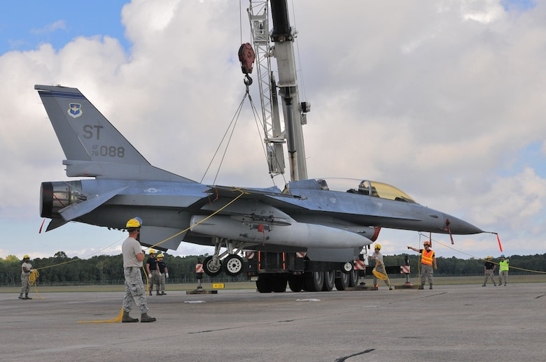 U.S. Air Force airmen from the New Jersey Air National Guard 177th Fighter Wing Crash Disabled Damaged Aircraft Recovery team maneuver an F-16 Fighting Falcon hooked up to a crane lift, Sept. 19, 2015, at Naval Air Station Wildwood Aviation Museum, N.J. The CDDAR team completed crane lift training, a tri-annual certification used in the event an immobile aircraft needs to be removed from a runway quickly and safely. (U.S. Air National Guard photo by Senior Airman Shane S. Karp / released)