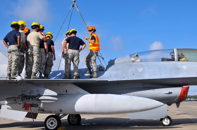 U.S. Air Force Master Sgt. Christopher Foye from the New Jersey Air National Guard 177th Fighter Wing Crash Disabled Damaged Aircraft Recovery team briefs the rest of his team on proper hook placement on the F-16 Fighting Falcon fuselage Sept. 19, 2015 at Naval Air Station Wildwood Aviation Museum, N.J. The CDDAR team completed crane lift training, a tri-annual certification used in the event an immobile aircraft needs to be removed from a runway quickly and safely. (U.S. Air National Guard photo by Senior Airman Shane S. Karp / released)