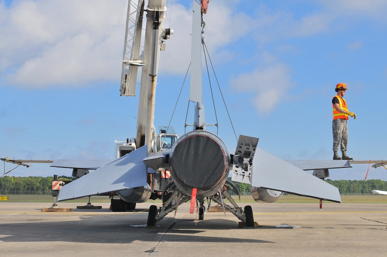 U.S. Air Force Master Sgt. Christopher Foye from the New Jersey Air National Guard 177th Fighter Wing Crash Disabled Damaged Aircraft Recovery team stands on the wing of an F-16 Fighting Falcon during CDDAR crane-lift training Sept. 19, 2015 at Naval Air Station Wildwood Aviation Museum, N.J. The CDDAR team completed crane lift training, a tri-annual certification used in the event an immobile aircraft needs to be removed from a runway quickly and safely. (U.S. Air National Guard photo by Senior Airman Shane S. Karp / released)