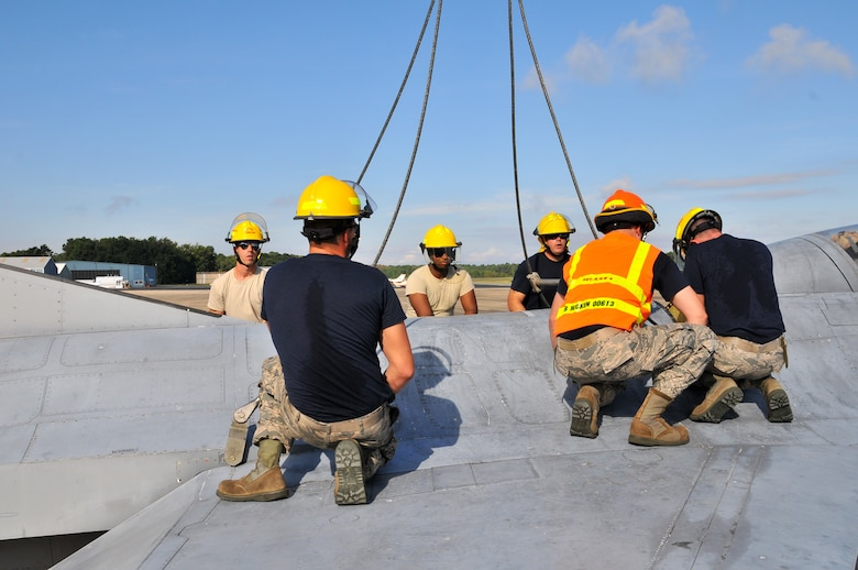 U.S. Air Force airmen from the New Jersey Air National Guard 177th Fighter Wing Crash Disabled Damaged Aircraft Recovery team work to hook a crane to an F-16 Fighting Falcon fuselage Sept. 19, 2015 at Naval Air Station Wildwood Aviation Museum, N.J. The CDDAR team completed crane lift training, a tri-annual certification used in the event an immobile aircraft needs to be removed from a runway quickly and safely. (U.S. Air National Guard photo by Senior Airman Shane S. Karp / released)