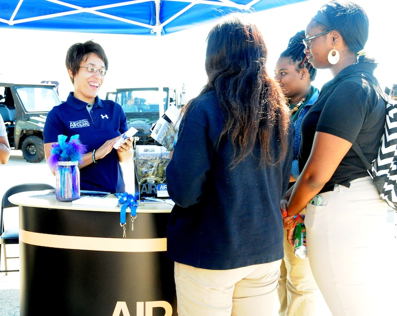Tech. Sgt. Nicolette Marshall, 113th Wing, D.C. Air National Guard recruiter, speaks with individuals attending the 2015 Andrews Air Show. Ma  as part of the Andrews Air Show Sept. 18. (U.S. Air National Guard photo by Senior Airman Erica Rodriguez)