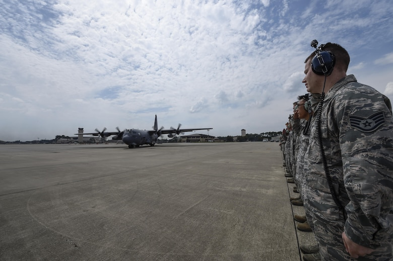 """Airmen with the 1st Special Operations Aircraft Maintenance Squadron render a salute to an AC-130U Spooky before its retirement flight at Hurlburt Field, Fla., Sept. 21, 2015. Tail number 0163, """"Bad Omen,"""" was retired Sept. 21, 2015, after more than 20 years of service. """"Bad Omen"""" last deployed to Bagram Airfield, Afghanistan in December 2013 where it accumulated approximately 600 combat hours and flew more than 100 sorties. (U.S. Air Force photo by Airman Kai White)"""