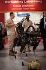 Lieutenant General Ronald L. Bailey (right), Deputy Commandant Plans, Polices, and Operations, and Captain Jim Pineiro (left), MCWL/FD Science and Technology Ground Combat Element branch head discuss the possible applications of the small robotic quadruped called Spot. The state-of-the-art robot could play an important role in MCWL/FD's continued exploration into unmanned systems and how they will shape tomorrow's future force.
