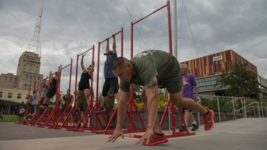 Gunnery Sgt. Orlando Flamenco a member of a combat logistic regiment at Marine Corps Base Camp Pendleton, Calif., drops down to do a burpee during a physical training event at Civic Space Park on Sept. 9, 2015, as part of Marine Week Phoenix. The event allows members of the community to join in and conduct the exercises alongside the Marines.