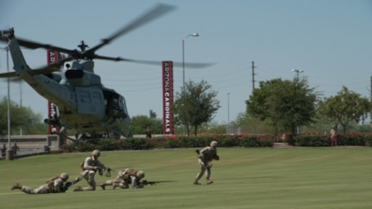 Marines rush from a UH-1Y Huey at the fields behind the University of Phoenix Stadium at Glendale, Arizona, Sept. 11, 2015. The demonstration was part of Marine Week Phoenix, which allows the Marine Corps to showcase its traditions, history, and values.