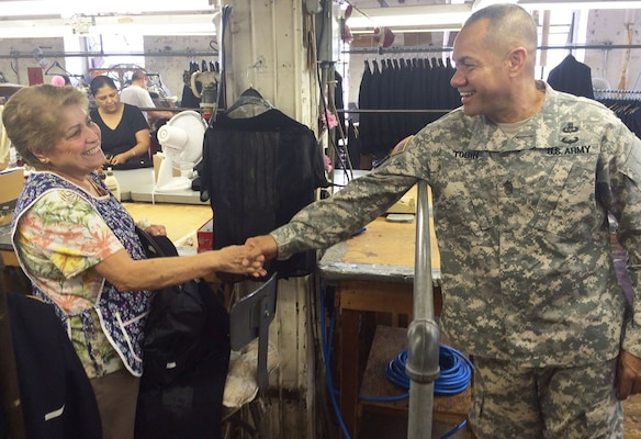 DLA senior enlisted leader Army Command Sgt. Maj. Charles Tobin, left, shakes hands with the longest-working employee at DeRossi & Son in Vineland, N.J., with 55 years on the job, during a visit to the Clothing and Textiles vendor's facility Aug. 19. Tobin also visited Crown Clothing in Vineland and the Federal Correctional Institution at Joint Base McGuire-Dix-Lakehurst, N.J.