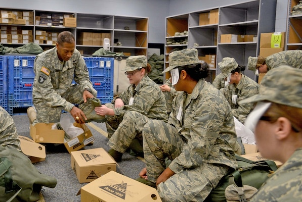 Army Brig. Gen. Charles Hamilton, DLA Troop Support commander, hands a pair of combat boots to an Air Force recruit receiving her initial clothing issue Aug. 6 at Lackland Air Force Base. Hamilton saw technology implemented by the Clothing and Textiles supply chain that helped cut the clothing issue time in half.