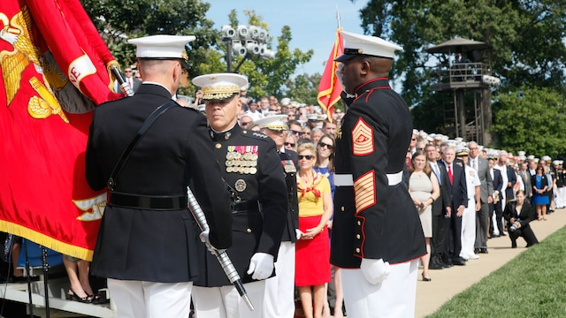 Gen. Joseph F. Dunford, Jr., the 36th and former Commandant of the Marine Corps, hands the Marine Corps Battle Colors to Gen. Robert B. Neller during their passage of command ceremony at Marine Corps Barracks Washington, D.C., Sept. 24, 2015. Gen. Dunford relinquished the position to Gen. Robert B. Neller, the 37th and new Commandant of the Marine Corps.