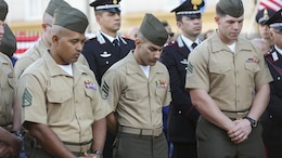 Marines with Special-Purpose Marine Air-Ground Task Force Crisis Response-Africa bow their heads in prayer during a September 11th remembrance ceremony in Nissoria, Italy, Sept. 22, 2015. The local priest offered a prayer as Americans and Nissorians remembered the shared pain of the lives lost that day 14 years ago.