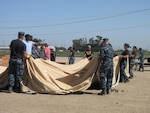 Members of the DLA Distribution Operations Team San Joaquin Navy Reserve unit work in unison with DLA Distribution Expeditionary team members at DLA Distribution San Joaquin, Calif., during the Expeditionary Academy. The team is working together in constructing the air beam tent.