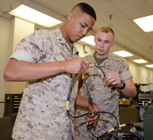 Lance Cpl. Iohnathan Morgan (left) and Lance Cpl. Jeremy Hayes, both ground radio intermediate repairers with Maintenance Company, Combat Logistics Battalion-451, conduct a function check on a Tactical Operations Center Intercommunication System at Marine Depot Maintenance Command during their annual training aboard Marine Corps Logistics Base Albany, Sept. 22.