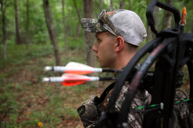 Cpl. Mitchell Teusch looks for a good place to set up his fall-restraint system during archery hunting season at Marine Corps Air Station Cherry Point, N.C., Sept. 22, 2015. A fall-restraint system catches you within a few feet to prevent hitting the ground when sitting on a tree stand. Hunting on Cherry Point is open to active duty personnel, their dependents, retirees, DOD employees and sponsored guests. Teusch is a quality assurance hydraulic mechanic with Marine Aircraft Group 14. (U.S. Marine Corps photo by Lance Cpl. Jason Jimenez/Released)