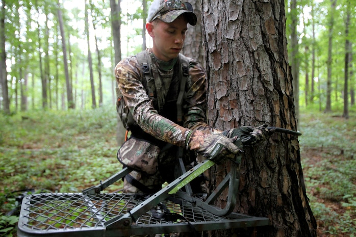 Cpl. Mitchell Teusch sets up his fall-restraint system during archery hunting season at Marine Corps Air Station Cherry Point, N.C., Sept. 22, 2015. A fall-restraint system protects the hunter from falling out of a tree stand. Hunting on Cherry Point is open to active duty personnel, their dependents, retirees, DOD employees and sponsored guests. Teusch is a quality assurance hydraulic mechanic with Marine Aircraft Group 14. (U.S. Marine Corps photo by Lance Cpl. Jason Jimenez/Released)