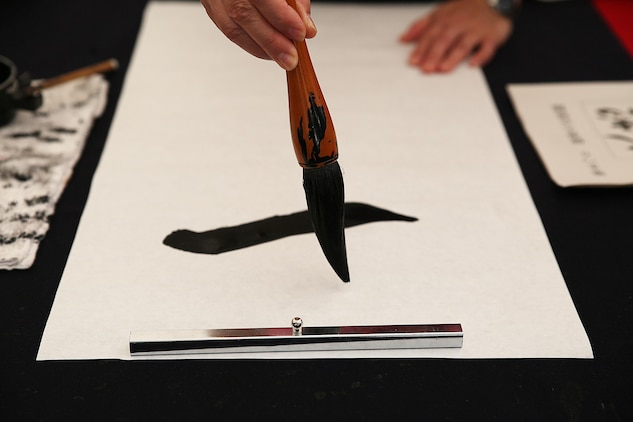 "A resident of Marine Corps Air Station Iwakuni, Japan, participate in a calligraphy contest during a cultural adaption program trip to the annual Japanese Calligraphy Brush Festival in Kumano, Hiroshima Prefecture, Sept. 23, 2015. Held in the capital of brushes, this city is home to approximately 1,500 ""fude-shi,"" brush-making craftsman and twenty master artisans of fude. This ancient tradition of Kumano-fude making dates back to the 18th century and became a way of life for villagers seeking income."