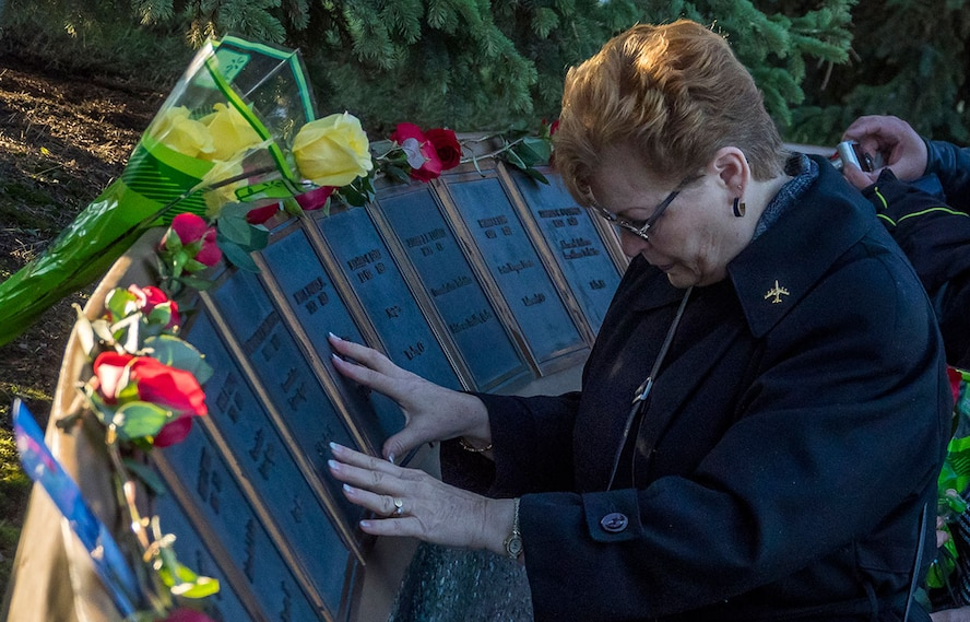 Linda DeFrancesco, mother of Senior Airman Lawrence DeFrancesco, places her hands on a plaque with her son's name on it during a quiet moment before a ceremony at the Yukla 27 memorial. American and Canadian airmen assigned to the 962nd Airborne Air Control Squadron, distinguished guests, and surviving family members of the crew of the E-3B Sentry, Airborne Warning and Control System aircraft, call sign Yukla 27, gathered for 20th anniversary memorial ceremonies on Joint Base Elmendorf-Richardson, Tuesday. On Elmendorf Air Force Base, Sept. 22, 1995, Yukla 27 from the 962nd Airborne Air Control Squadron encountered a flock of geese and crashed shortly after takeoff on a routine surveillance training sortie, killing all 24 U.S. and Canadian Airmen aboard. (U.S. Air Force photos/Justin Connaher)