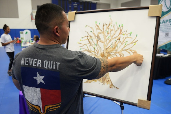"A Team Andersen member leaves a fingerprint on the ""Tree of Life"" artwork Sept. 24, 2015, at Andersen Air Force Base, Guam. Individuals were invited to leave a finger print leaf if suicide or domestic violence has ever impacted their lives.  Representatives from the 36th Medical Operations Squadron held activities throughout September to raise awareness for suicide prevention and domestic violence. (U.S. Air Force photo by Senior Airman Joshua Smoot/Released)"
