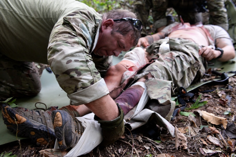 A service member from the Special Operations Command Forward (Central America) creates a makeshift splint during a personnel recovery exercise Sept. 13, 2015, near Soto Cano Air Base, Honduras. The six-man team rescued three simulated casualties during the exercise. (U.S. Air Force photo by Staff Sgt. Jessica Condit)