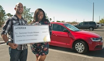 Carlos Del Valle, 99th Force Support Squadron Outdoor Recreation Center outdoor adventure programmer, poses with a $2,500 check presented to him by Takeira Jones-Bolden, 99th FSS supervisory marketing specialist and commercial sponsorship coordinator, in front of the brand new 2015 Volkswagen Jetta he won at Nellis Air Force Base, Nev., Sept. 23, 2015. Del Valle won the 99th FSS' Ultimate Summer Giveaway grand prize of the new car by having his name drawn during the car's raffle. Del Valle was one of almost 10,000 Nellis and Creech AFB members who entered the drawing, which began in June. In addition to winning the car, Del Valle also was given $2,500 spending cash to pay for the car's tax, title and licensing fees. (U.S. Air Force photo by Staff Sgt. Siuta B. Ika)