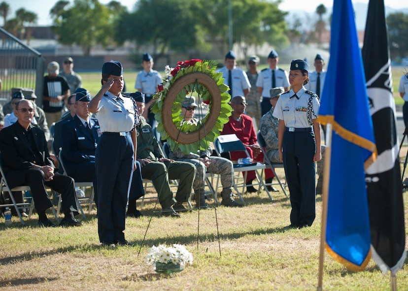 An Air Force Junior ROTC cadet from Rancho High School, Las Vegas, salutes a wreath during the Prisoners of War/Missing in Action Recognition Ceremony at Nellis Air Force Base, Nev., Sept. 18, 2015. During the ceremony, JROTC cadets placed white daisies on the wreathe while the names of deceased POWs and those still MIA were read aloud. (U.S. Air Force photo by Staff Sgt. Siuta B. Ika)