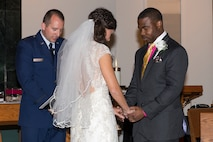 Chaplain (Capt.) Eli Dowell, 375th Air Mobility Wing chaplain, prays with a couple being married at the Scott Air Force Base chapel. Dowell provides pastoral care, counseling and religious education to Scott personnel and their families. (U.S. Air Force Photo by Senior Airman Megan Friedl)