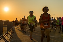 Runners cross the taxiway on the flightline at Barksdale Air Force Base, La., Sept. 19, 2015, during the 2015 Half Marathon and 5K hosted by the 2nd Force Support Squadron. Nearly 300 participants from on and off base, including runners aged 9-69, as well as kids on bikes and others towed in strollers and wagons, joined to race. (U.S. Air Force photo/Staff Sgt. Tyler Prince)