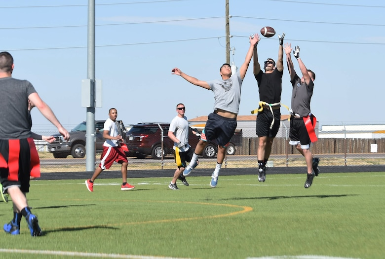 Team Buckley members jump in the air to catch the football during a flag football game Sept. 23, 2015, at the all-purpose field on Buckley Air Force Base, Colo. The game was a chance for junior enlisted members to engage in friendly competition against the Buckley 5/6 Association, while allowing NCOs the opportunity to mentor younger Airmen in a non-professional setting.  (U.S. Air Force photo by Airman 1st Class Samantha Meadors/Released)
