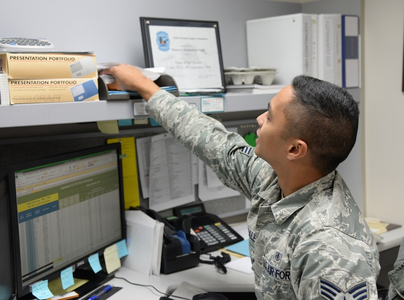 U.S. Air Force Senior Airman Noel Morales, a 354th Medical Support Squadron uniform business office manager, reaches for checks Sept. 23, 2015, at Eielson Air Force Base, Alaska. Morales receives checks from health insurance companies as part of the reimbursement program for care provided to non-active duty patients that have insurance other than TRICARE. (U.S. Air Force photo by Airman 1st Class Cassandra Whitman/Released)