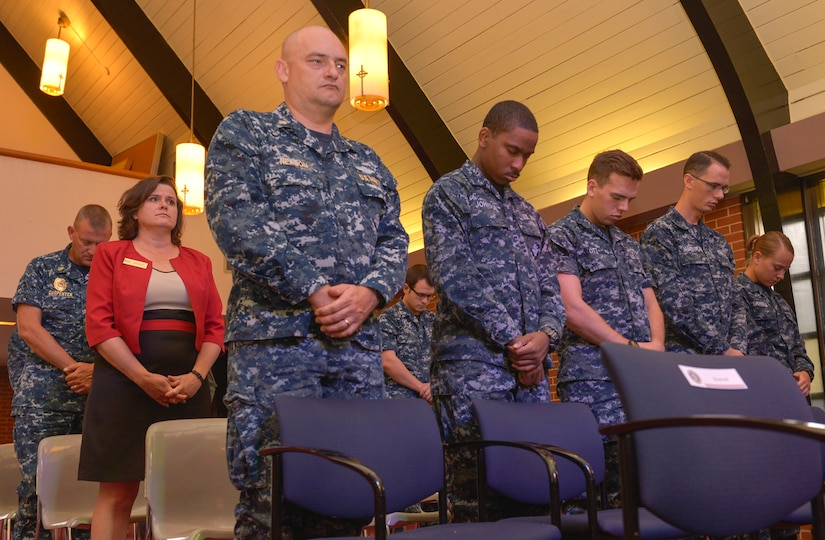 Bowing their heads, during the Navy Gold Star Remembrance ceremony both civilian and service members stand together at Good Shepherd Chapel Sept. 23, 2015 on Joint Base Charleston –Weapons Station, Charleston, S.C. The event honors local fallen Sailors.