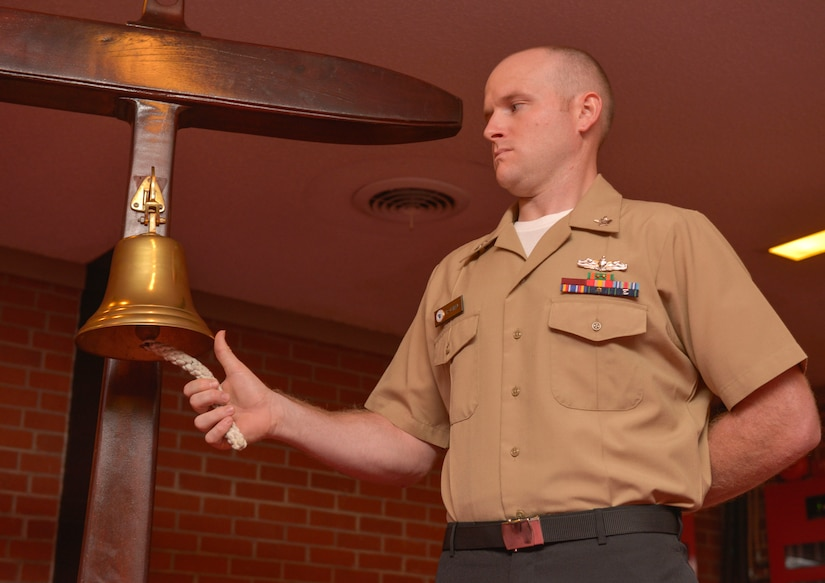 Navy Information Systems Technician, 2nd Class Seth Oswald prepares to ring the bell during the Navy Gold Star remembrance ceremony Sept. 23, 2015at Good Shepherd Chapel on Joint Base Charleston –Weapons Station, Charleston, S.C. The event honors local fallen Sailors. Oswald rang the bell each time one of the deceased Sailor's names was read.