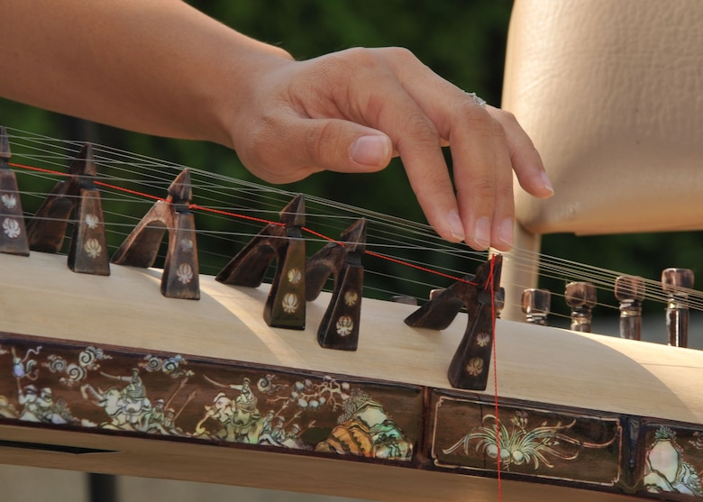 The intricate design work on a dan tranh, or Vietnamese zither, is seen up close as Kimloan Le, 61st Force Support Squadron, performs an instrumental piece during the 2015 Space and Missile Systems Center's Diversity Day event, Sept. 23 in the courtyard of the Schriever Space Complex at Los Angeles Air Force Base in El Segundo, Calif. (U.S. Air Force photo/Sarah Corrice)