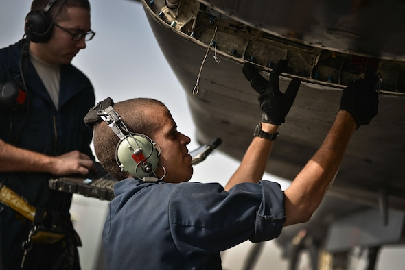Airman 1st Class Bobby Baker and Brian Allen, 37th Aircraft Maintenance Unit crew chiefs, read through their technical orders during preventative maintenance on a B1-B Lancer September 22, 2015 at Al Udeid Air Base, Qatar. Baker and Allen are deployed from Ellsworth Air Force Base, S.D. (U.S. Air Force photo/Staff Sgt. Alexandre Montes)