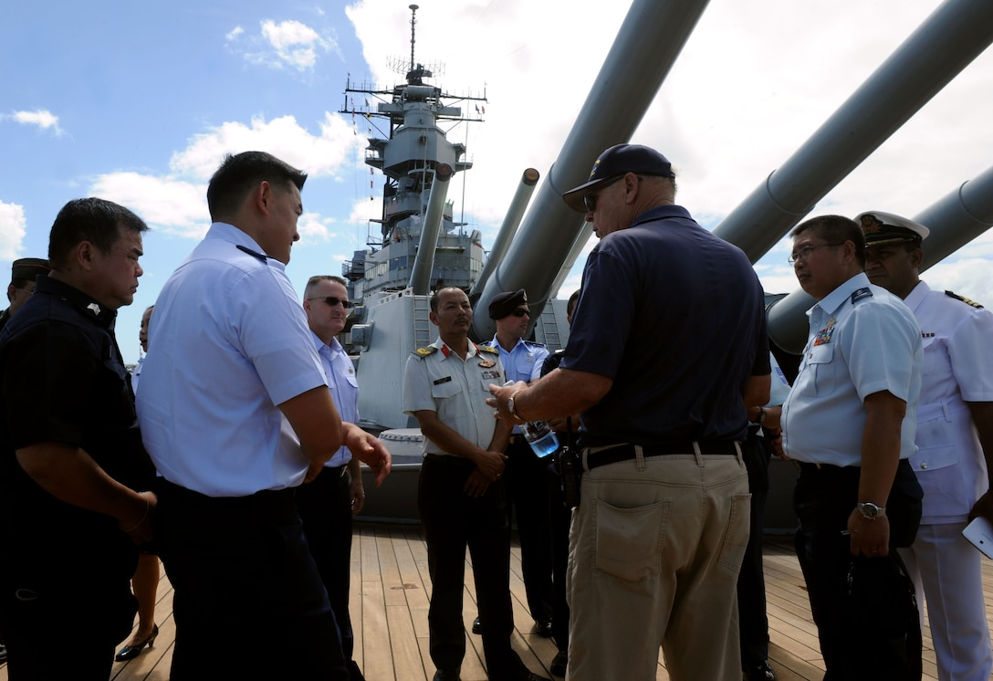 Pacific Rim Airpower Symposium attendees listen to a tour guide aboard the USS Battleship Missouri Memorial during a tour of Pearl Harbor historic sites Sept. 22, 2015, in Honolulu, Hawaii. Senior officer and enlisted airmen from nations throughout the Indo-Asia-Pacific region attended the symposium to discuss ways to improve cooperation, leadership and coordination efforts. (U.S. Air Force photo by Staff Sgt. Alexander Martinez/Released)