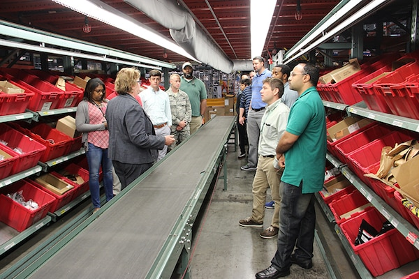 """Sherre Mitten-Bell (left in gray), DLA Distribution Susquehanna public affairs officer, shows DLA Troop Support Industrial Hardware employees, the """"pick and pack"""" area at the warehouse facility in New Cumberland, Pennsylvania during a visit Sept. 16. DLA IH employees visited the warehouse to get a better understanding of the process of getting material to the warfighter once the contract is awarded."""