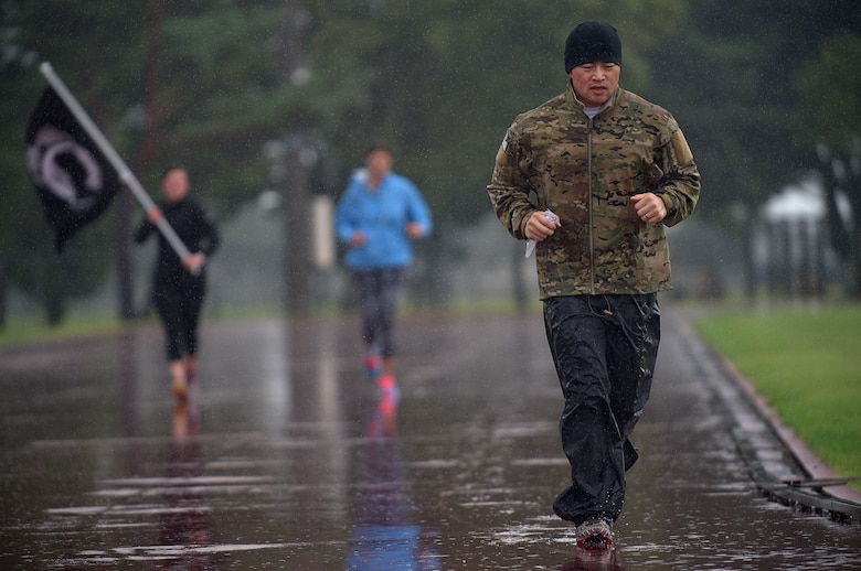 Capt. Michael Gruber, the 35th Communications Squadron director of operations, reaches his 65th mile while running in a downpour of rain Sept. 18, 2015, at Misawa Air Base, Japan. Beginning his ultramarathon at 5 p.m. on Sept. 17, 2015, Gruber's goal was to run 100 miles in a span of 24 hours at the local high school track. (U.S. Air Force photo/Senior Airman Jose L. Hernandez-Domitilo)