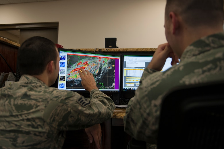 U.S. Air Force Staff Sgt. Mark Bratic, left, 23d Operations Support Squadron NCO in charge of airfield weather, briefs Airman 1st Class Lucas Payne, 23d OSS weather technician during a shift change Sept. 21, 2015, at Moody Air Force Base, Ga. Forecasters conduct these briefs to incoming shift members to inform them of what the weather forecast status in the last eight hours and what is expected to happen in the next 24 hours. (U.S. Air Force photo by Airman 1st Class Kathleen D. Bryant/Released)