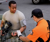 Senior Airman Paul Byous, 51st Civil Engineer Squadron firefighter, has his blood pressure checked by a Korean emergency medical technician Sept. 24, 2015, near Songtan, Republic of Korea. Byous and more than 25 other members of the 51st CES from Osan Air Base participated in a joint-training exercise involving a simulated hazardous materials spill. (U.S. Air Force photo by Staff Sgt. Benjamin Sutton)