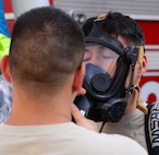 An Airman assigned to the 51st Civil Engineer Squadron's emergency management response team assists Staff Sgt. Jeffrey Williams, 51 CES emergency management plans and programs, with removing his respirator Sept. 24, 2015, near the city of Songtan, Republic of Korea. Airmen took advantage of a unique training opportunity to train in a simulated hazardous materials environment. (U.S. Air Force photo by Staff Sgt. Benjamin Sutton)