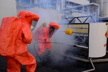 Two emergency first responders from the Songtan fire department plug a hole during a simulated hazardous material training event Sept. 24, 2015, near Songtan, Republic of Korea. The South Korean agencies invited members of Osan Air Base's 51st Civil Engineer Squadron to the unique training event. (U.S. Air Force photo by Staff Sgt. Benjamin Sutton)